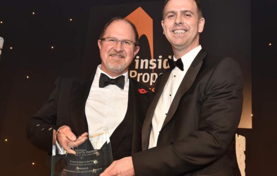 2 men in tuxedos holding an award