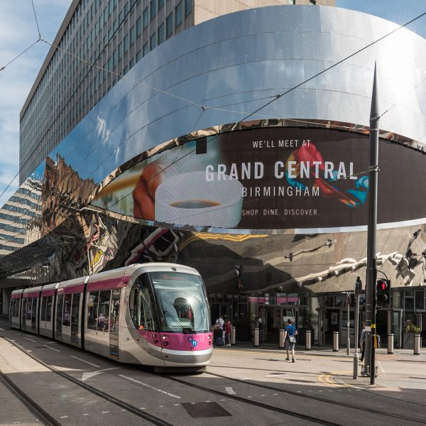 Metro tram passing a building